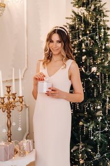自宅のクリスマスツリーの近くで彼女の手にクリスマスプレゼントとピンクのドレスの笑顔の女の子の肖像画