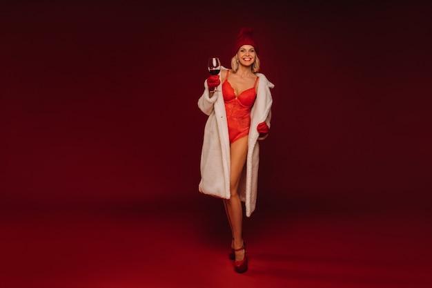 백색 모피 코트와 속옷 빨간색 배경에 샴페인 한 잔을 들고 웃는 여자의 초상화.