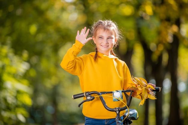 フレンドリーな手を振って秋の公園で自転車と黄色のスウェットシャツの笑顔の女の子の肖像画。