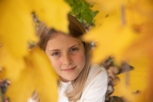 黄色のカエデの葉で微笑んでいる女の子の肖像画