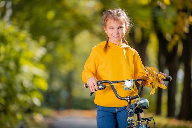 秋の公園で自転車と黄色のスウェットシャツの笑顔の女の子の肖像画。