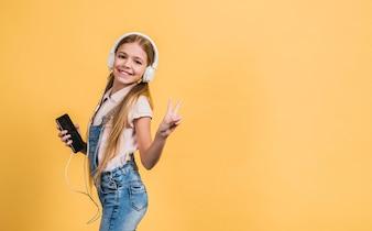 Портрет улыбающейся девушки, слушающей музыку на белых наушниках, жестикулирующих против желтого фона