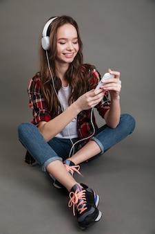 Портрет улыбающейся девушки, слушающей музыку на телефоне