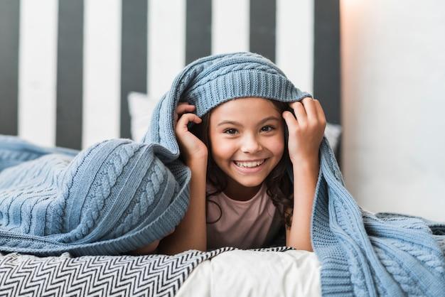 ベッドに毛布の下で彼女の兄弟と横たわっている笑顔の女の子の肖像