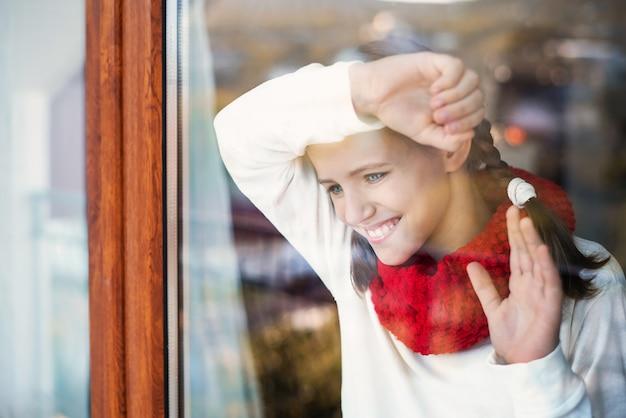 手を振って窓の外の笑顔の女の子の肖像画。