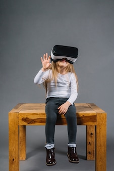 Portrait of a smiling girl sitting on table wearing virtual reality glasses touching in the air