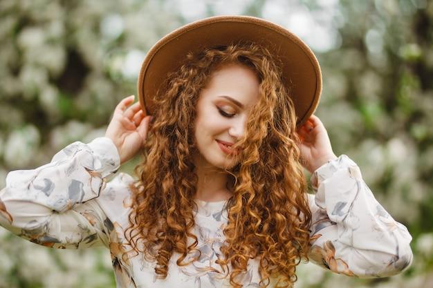 ベージュの帽子と白いドレスを着て笑顔の女の子の肖像画は、晴れた新鮮な日に新鮮な緑の庭で春を楽しんでいます。季節はコンセプトを変えます。