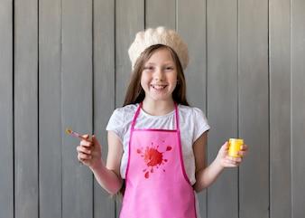 Портрет улыбающейся девушки в вязаной шапке с кисточкой и желтой краской в руках