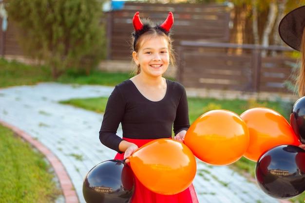 Портрет улыбающейся девушки с темными волосами в костюме хэллоуина, держащей оранжевые и черные воздушные шары на открытом воздухе.