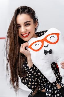Портрет улыбающейся девушки с мягкой игрушкой в руках. мягкая игрушка в форме зуба.