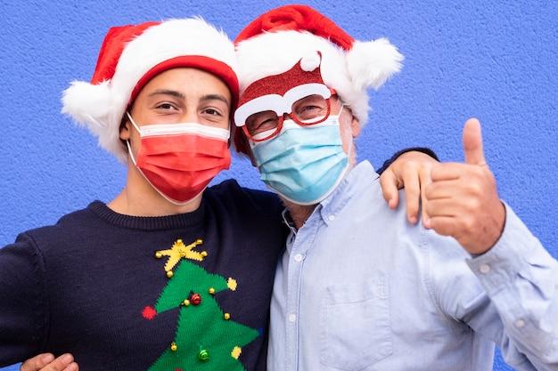 코로나바이러스와 산타 모자로 인해 마스크를 쓰고 손으로 괜찮게 하는 10대 손자를 껴안고 있는 웃는 할아버지의 초상화. 가족의 개념과 미래에 대한 긍정적인 희망