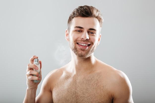 Портрет улыбающегося полуголого мужчины, распыляющего духи