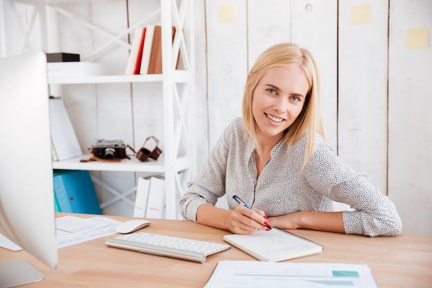 Портрет улыбающейся счастливой деловой женщины, сидящей на своем рабочем месте и делающей заметки