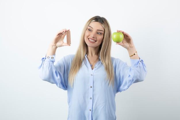 白い壁にチョコレートバーと青リンゴを保持している笑顔の幸せな女の子の肖像画