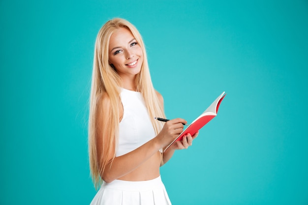 Портрет улыбающейся счастливой девушки, делающей заметки в записной книжке, изолированной на синем фоне