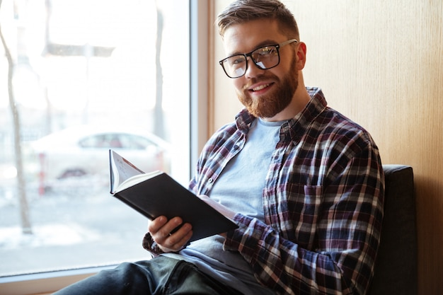 本を持って笑顔の幸せな男性学生の肖像画