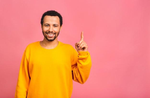 핑크 위에 절연 제쳐두고 손가락으로 캐주얼 가리키는 웃는 행복 한 남자의 초상화.
