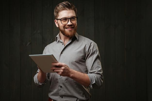 Портрет улыбающегося счастливого человека в очках, держащего планшетный компьютер и смотрящего в сторону, изолированного на черной деревянной поверхности