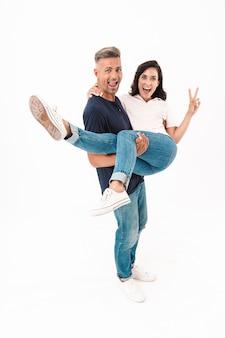 Портрет улыбающейся счастливой позитивной взрослой любящей пары, изолированной над белой стеной, весело проводящей время.