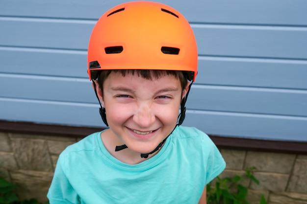 オレンジ色のスポーツクラッシュヘルメットを身に着けている笑顔の幸せな10代の白人少年の肖像画、夏に自転車やスケートボードに乗ることを学び、屋外の子供たちの活動中に安全と保護。