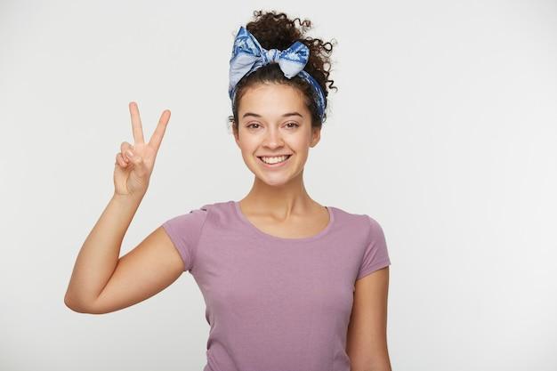 승리 기호를 보여주는 웃는 행복 한 여자의 초상화