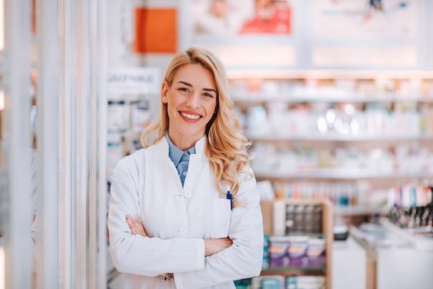 Портрет усмехаясь работника здравоохранения в современной аптеке.