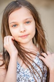 Портрет улыбающейся маленькой красивой девочки с длинными волосами. девочка 7-9 лет руками у лица. молодость, свежесть.