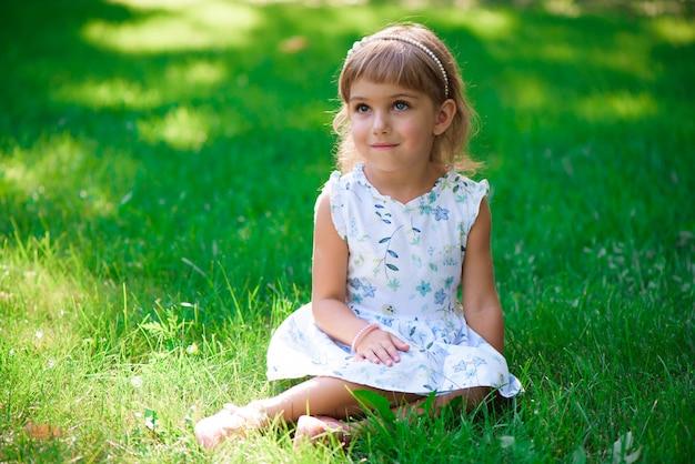 푸른 잔디에 앉아 웃는 어린 소녀의 초상화.