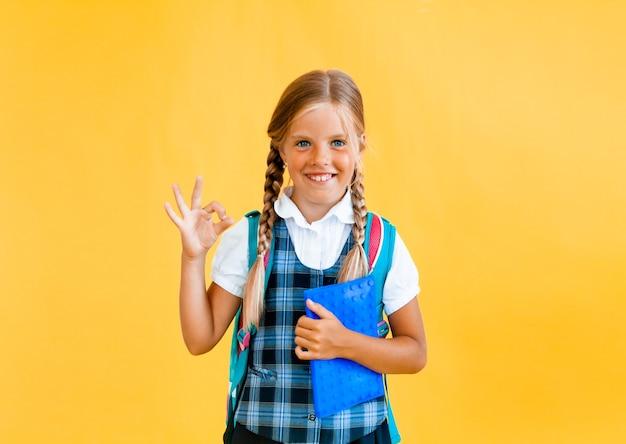 Портрет улыбающейся маленькой школьницы с рюкзаком, держащей тетрадь на желтом фоне