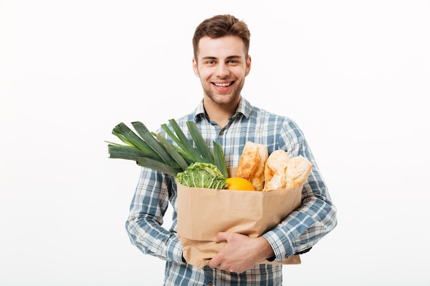Портрет улыбающегося человека, держащего бумажный пакет