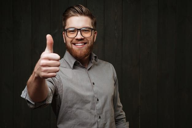 Портрет улыбающегося человека в очках, показывающего большой палец вверх, изолированного на черной деревянной поверхности