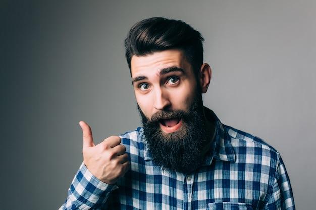 灰色の壁の上に親指を示す眼鏡の笑顔の男の肖像画