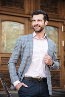 Портрет улыбающегося человека в куртке, создавая на открытом воздухе