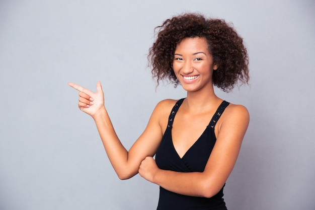 Портрет улыбающегося человека, указывающего пальцем на серую стену