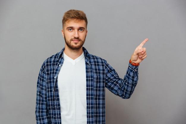 Портрет улыбающегося человека, указывающего пальцем вверх, изолированного на серой стене
