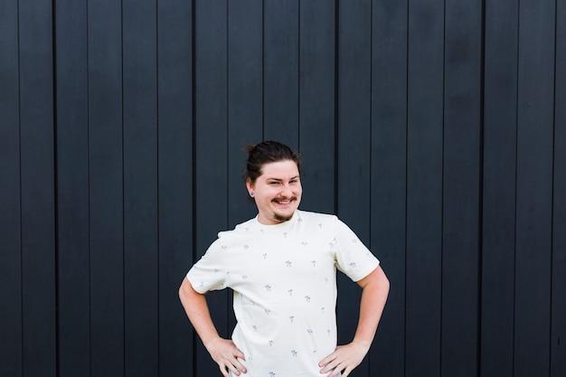 Портрет улыбающегося человека с его руки на бедре против черной деревянной стены
