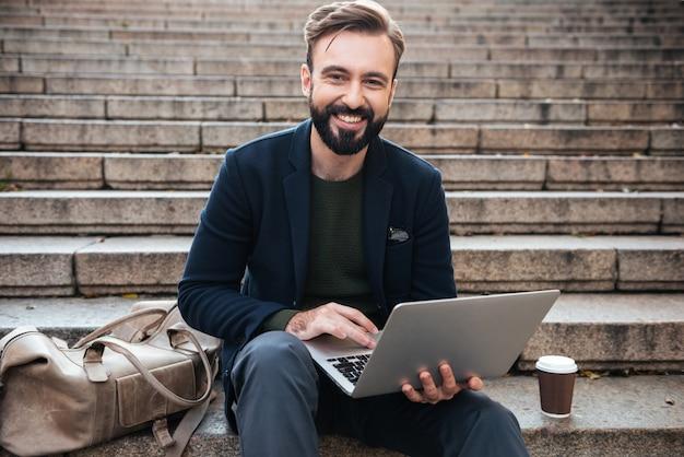 Портрет улыбающегося человека, работающего на ноутбуке
