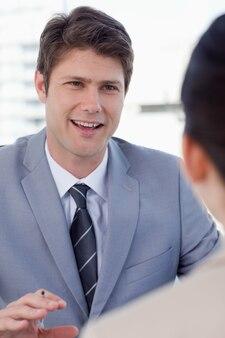 Портрет улыбающегося менеджера, интервьюирующего женщину-заявителя