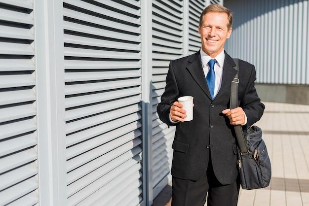 Портрет улыбающегося зрелого бизнесмена с чашкой кофе