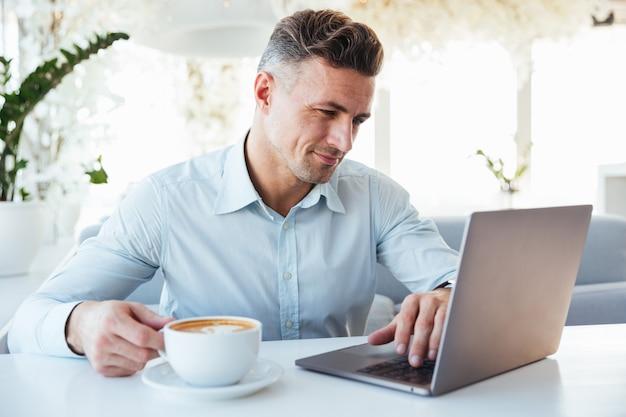 Портрет улыбающегося зрелого человека с помощью ноутбука