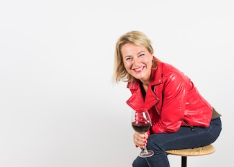 Portrait of a smiling mature woman sitting in stool holding wine glass in hand
