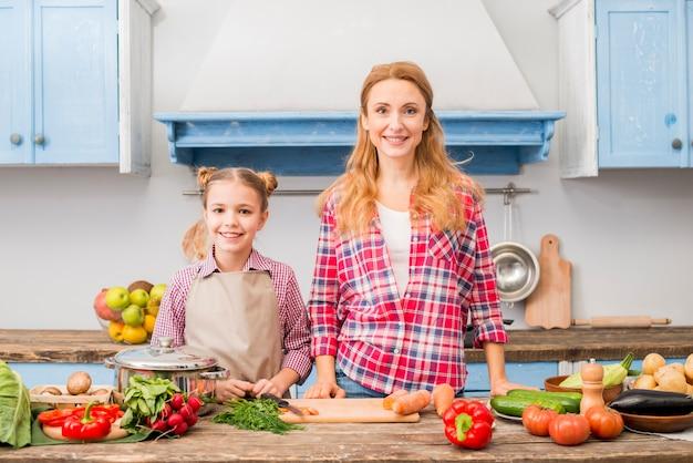 야채와 함께 테이블 앞에 서 웃는 어머니와 그녀의 딸의 초상화