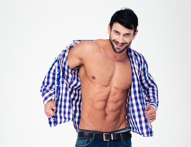 Портрет улыбающегося мускулистого мужчины, раздевающего рубашку, изолированного на белой стене