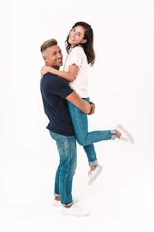 Портрет улыбающейся оптимистичной взрослой влюбленной пары, изолированной над белой стеной, весело проводящей время.