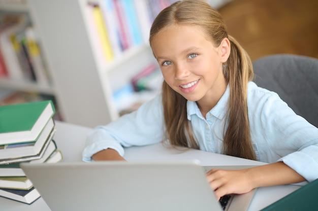 Портрет улыбающегося довольного красивого молодого кавказского школьника с хвостиками, сидящего за ноутбуком