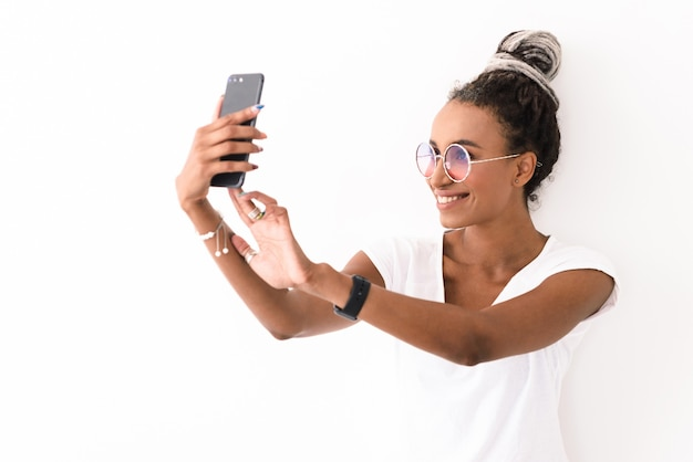 白で隔離された恐怖のポーズで笑顔のポジティブな若い女性の肖像画は、携帯電話で自分撮りを取ります。