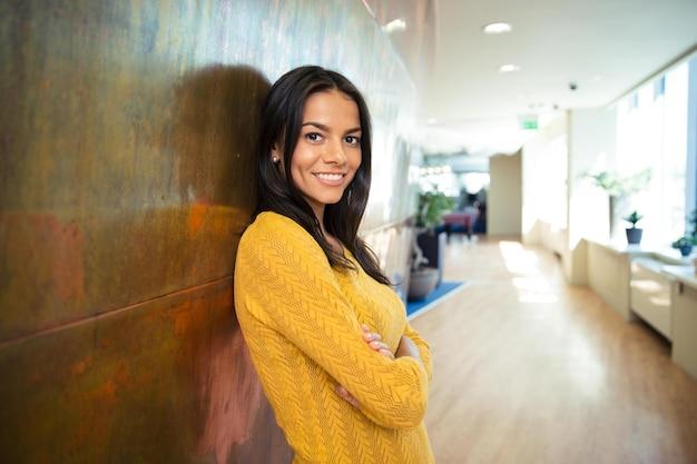 Портрет улыбающейся красивой деловой женщины, стоящей со сложенными руками в коридоре