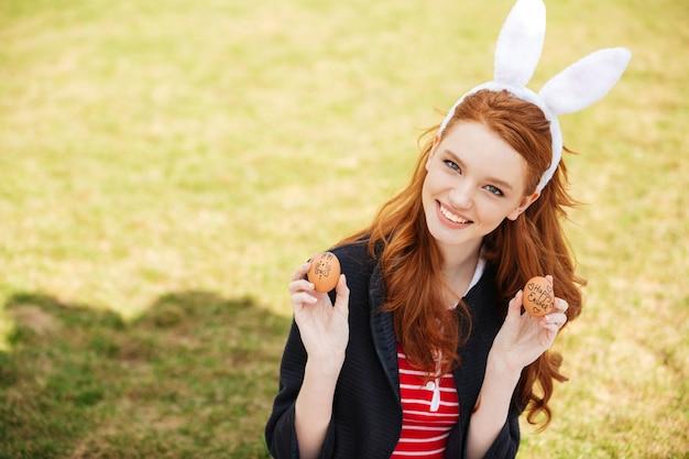 Портрет улыбающейся рыжеволосой женщины в ушах зайчика