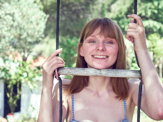 나무 계단의 단계 사이에 그녀의 얼굴을 가진 웃는 redheaded 러시아 여자의 초상화. 여름 분위기