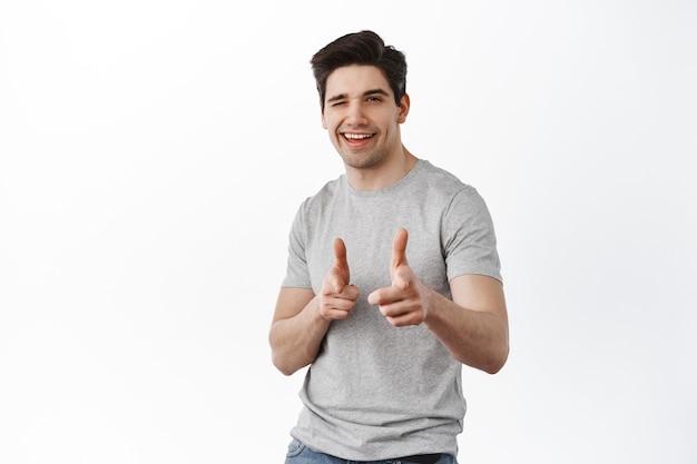 Портрет улыбающегося довольного мужчины в футболке, указывающего на перед, изолированного на белой стене